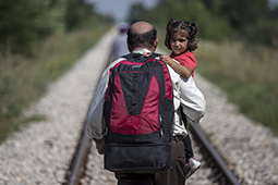 A migrant, hoping to cross into Hungary, carries a child as he walks along a railway track outside the village of Horgos in Serbia, towards the border it shares with Hungary August 31, 2015. REUTERS/Marko Djurica      TPX IMAGES OF THE DAY